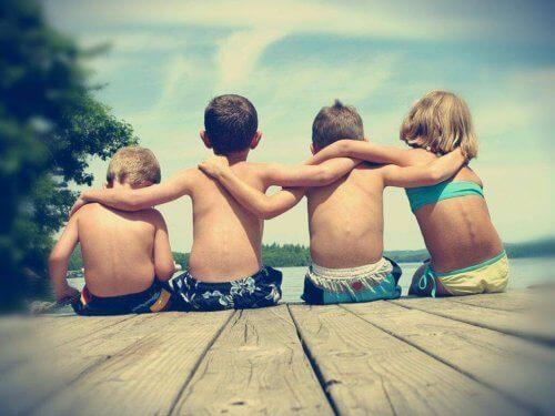 sırtı dönük deniz kenarında kol kola oturan dört çocuk