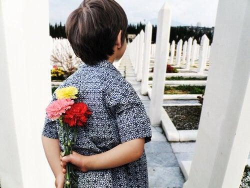arkasında çiçek tutan çocuk