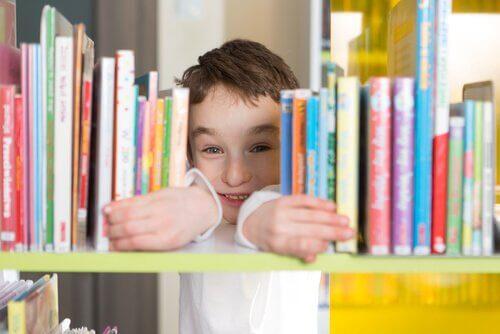 kitapların arasından bakan çocuk