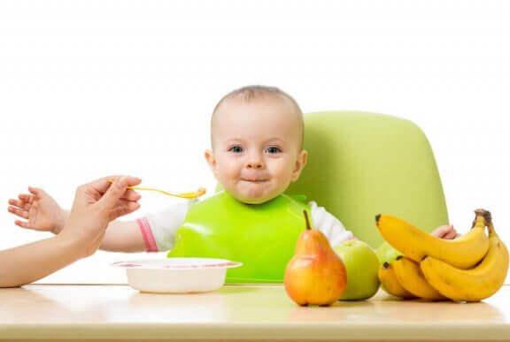 yeşil önlüklü mutlu yemek yiyen bebek