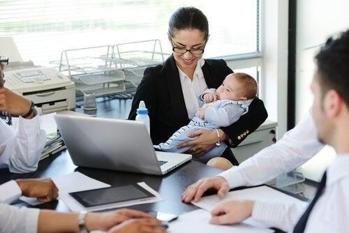 bebeği kucağında çalışan kadın