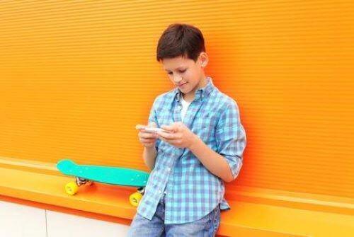 telefona bakan kaykaylı çocuk
