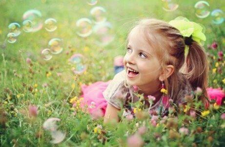 çimde baloncuklarla oynayan kız çocuğu