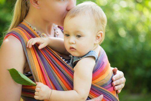 Bebek taşıma kangurusundaki bebeğini öpen anne