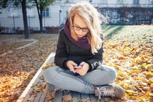 Sonbaharda parkta telefonuna bakan kız