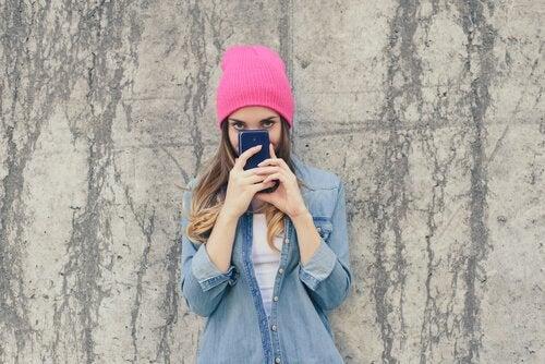 Duvara dayanmış fotoğraf çeken pembe bereli kız