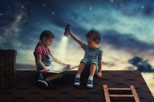 Karanlıkta damda fener ışığında kitap okuyan çocuklar