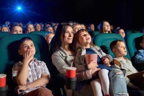Sinema salonunda çocuk filmleri izleyen anne ve çocuklar