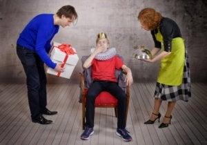 Tahtta oturmuş anne babasından hediye bekleyen şımarık çocuk