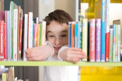 Kütüphanede kitaplar arasından gülümseyen çocuk