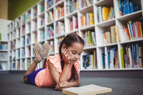 Kütüphanede yatarak kitap okuyan bir kız