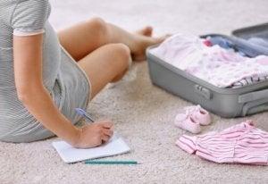 Bebek bavulunun önünde oturup not alan anne