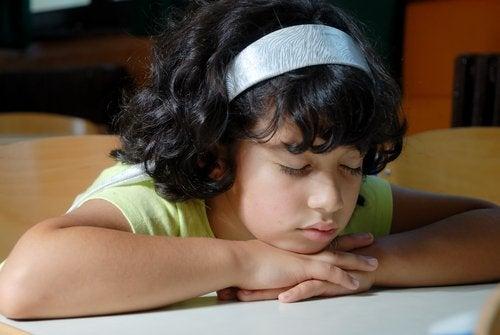 Eli çenesinde sırada uyuyan çocuk