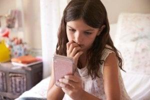 Tırnaklarını yiyerek telefonuna bakan kız