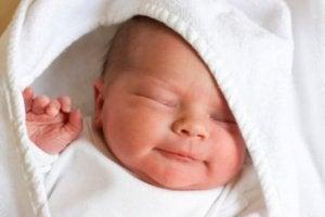 Gülümseyerek kundakta uyuyan bebek