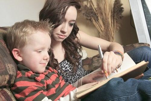 Annesiyle kitap okuyan sarışın çocuk