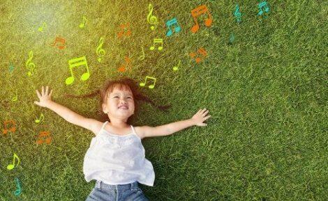 Çimlere uzanan kafasında notalar uçuşan çocuk