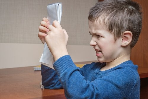 elindeki deftere sinirli bir şekilde bakan çocuk