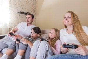 Anne ve baba çocuklarıyla video oyunu oynuyor