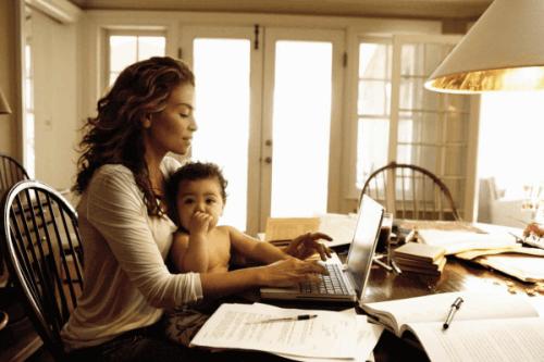 Evde bebeği kucağında bilgisayarda iş yapan anne