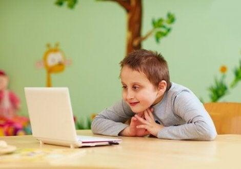 Gülümseyerek bilgisayara bakan çocuk