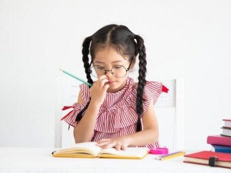 Masada ders çalışan gözlüklü örgülü kız