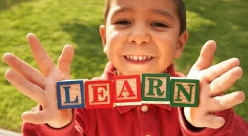 Çocuk öğrenmek yazan küpleri tutuyor