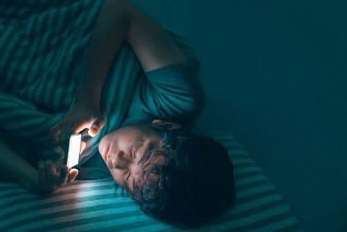 Gece cep telefonu ile ilgilenen genç