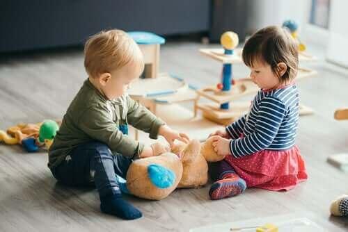 İki bebek ayıcıkla oynuyor