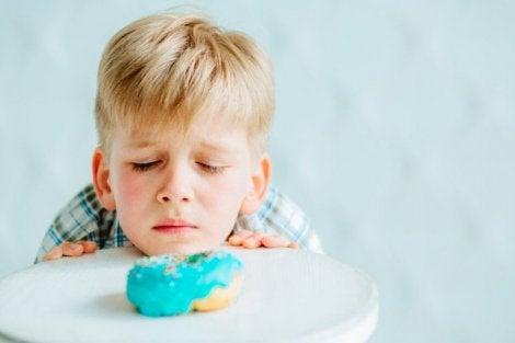 Gluten intoleransı yüzünden üzülerek keke bakan çocuk