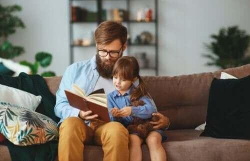 Kanepede babasıyla sarılarak kitap okuyan kız
