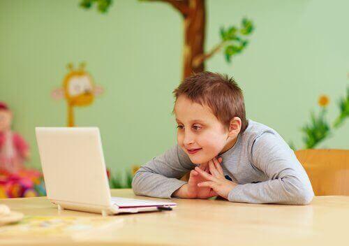 Gülümseyerek bilgisayara bakan özel ihtiyaçları olan çocuk