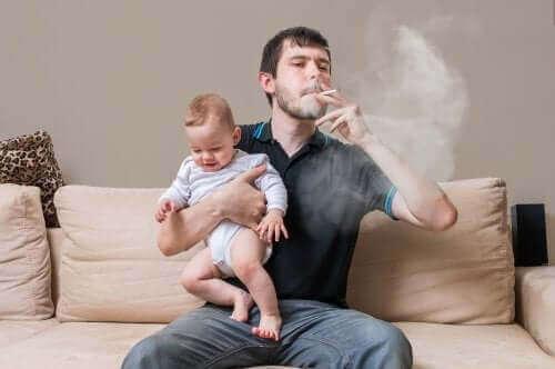 kucağında çocuğu ve sigara içen baba