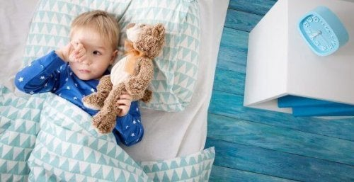 Ayıcığı ile yatakta yatan bebek