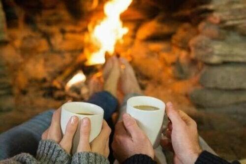 şömine karşısında kahve içen çift