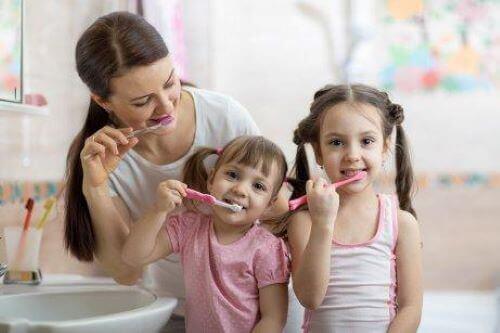 dişlerini fırçalayan anne ve çocuklar