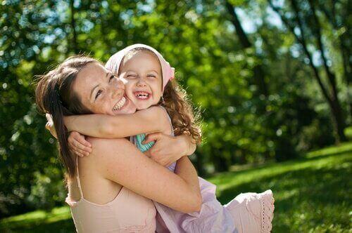 Kızını kucaklayan anne gülüyor