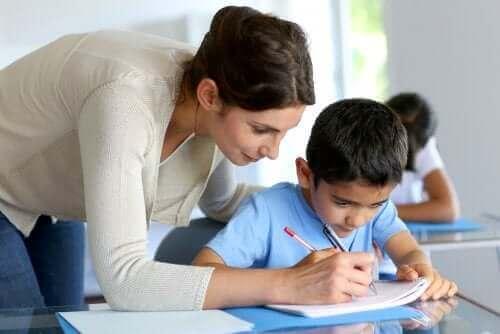 Sınıf tekrarı yapan öğrenciye yardım eden öğretmen