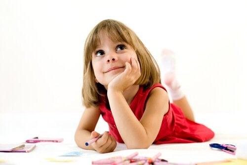 Yere uzanmış çizim yaparken düşünen çocuk