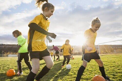 futbol oynayan küçük kızlar ve erkekler