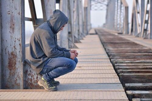 Tren yolunda çökmüş sigara içen adam