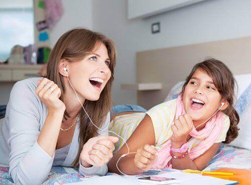 Bir kulaklığı paylaşarak kızıyla müzik dinleyen anne