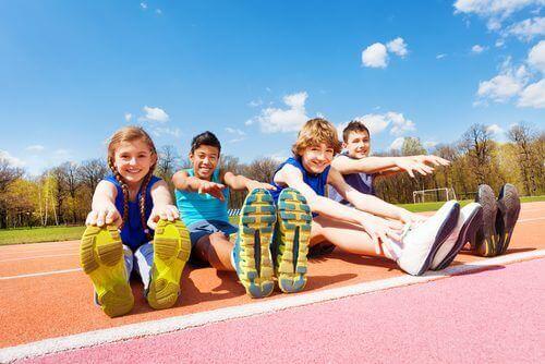 Spor sahasında esneme yapan çocuklar