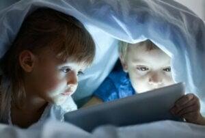 Yorganın altında tablete bakan çocuklar