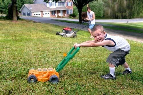 Babasını taklit ederek çim biçiyor gibi yapan çocuk