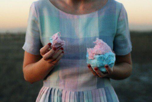 Yediği pamuk şekerle aynı tonda pembe ve mavi elbise giyen kadın