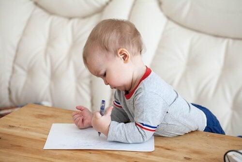Sehpada resim çizmeye çalışan bebek