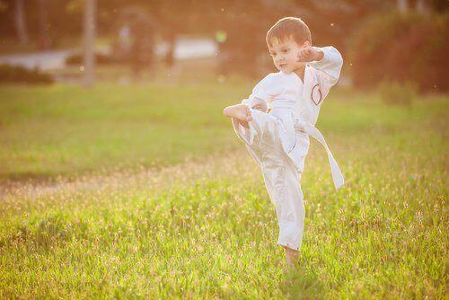 Çimenlikte dövüş sporu yapan küçük erkek çocuk
