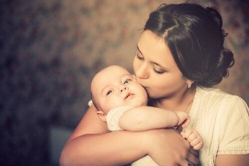 Annelik içgüdüsü ile çocuğunu öpen anne