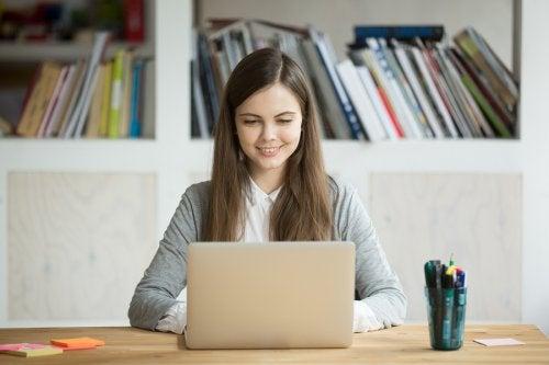 Masada oturmuş bilgisayara bakarak gülümseyen kız